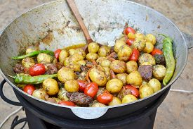 stock photo of cauldron  - Big cauldron with roasted potato - JPG