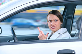 foto of middle finger  - angry woman in a car is showing her middle finger - JPG