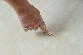picture of grout  - Workers hand smoothing the grout joints between tiles using a rubber stick - JPG