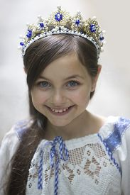 image of toddlers tiaras  - Portrait of pretty smiling princess girl with long brunette hair in traditional ukrainian embroidery white blue colors and beautiful diadem with diamonds in gold looking forward vertical picture - JPG