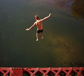 image of trestle bridge  -  a boy jumping of an old train trestle bridge into a river toned with a retro vintage instagram filter effect app or action on a hot summer day - JPG