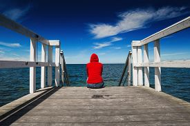 image of jetties  - Alone Young Woman in Red Hooded Shirt Sitting at the Edge of Wooden Ocean Jetty Looking at Water  - JPG