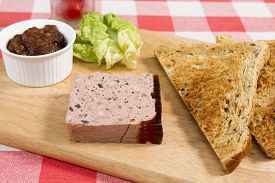 foto of canard  - Ardennes pate on a wooden board with pickle - JPG