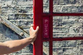 pic of phone-booth  - A young female hand is opening the door of a red phone booth - JPG