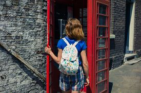 image of phone-booth  - A young woman is entering a traditional red english phone booth on a sunny day - JPG