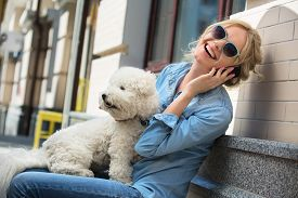 picture of bichon frise dog  - Cute blonde in sunglasses and a bright blue denim shirt emotionally talking on a cell phone - JPG