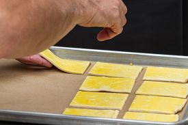 picture of pastry chef  - close up of a chefs hands placing prepared puff pastry on a tray for baking - JPG