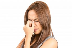picture of frown  - Close up portrait of frowning Asian woman light brown hair in sleeveless gray dress pinching nose in pain and discomfort from sinus problem or throbbing headache - JPG