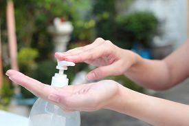 picture of gels  - Female hands using gel pump dispenser wash hand sanitizer - JPG