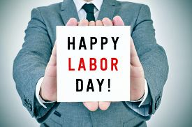 image of labor  - closeup of a young man in suit showing a signboard with the text happy labor day written in it - JPG