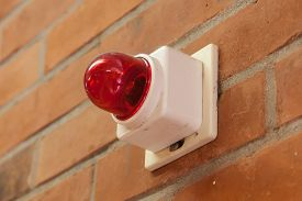 foto of emergency light  - Red emergency light on a brick wall selective focus - JPG