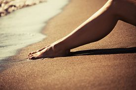 picture of barefoot  - woman barefoot legs on sand beach by the sea at sunset - JPG