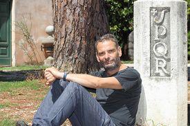 foto of spqr  - man sitting by Rome symbol SPQR Senatus Populusque Romanus - JPG