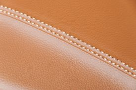 image of stitches  - orange car leather interior details with stitch - JPG