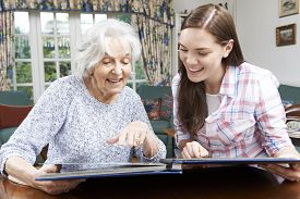 pic of grandmother  - Grandmother Looking At Photo Album With Teenage Granddaughter - JPG