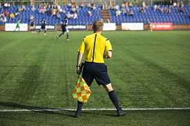 image of referee  - Assistant referees with flag on the soccer match - JPG