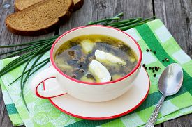 stock photo of sorrel  - Sorrel soup with egg and greens on a wooden background - JPG