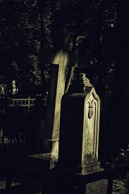 stock photo of tombstone  - Tombstones in a shade on an old cemetery - JPG