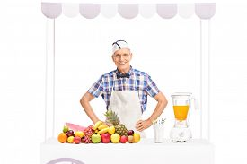 pic of jerks  - Mature soda jerk in white apron standing behind a stand full of fresh fruits isolated on white background - JPG