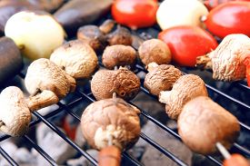 stock photo of charcoal  - fresh raw tomatoes onion mushroom eggplant on skewers over charcoal on grid over brazier grill - JPG