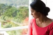 Thoughtful young woman looking through window at home poster