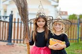 Cute little witches with broom and treats on background of house poster