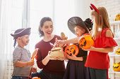Happy family celebrating Halloween! Young mom treats children with candy. Funny kids in carnival cos poster