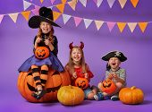 Happy brother and two sisters at Halloween. Funny kids in carnival costumes on background of purple  poster