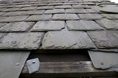 picture of shingles  - broken and fallen slate leaves hole in a roof due to storm or decay - JPG