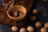Walnut kernels in wooden bowl and whole walnuts on blue slate surface. Healthy nuts and seeds compos poster