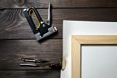Stretching Cotton Canvas On Wooden Stretcher Bar, Stapler And Canvas Pliers On A Brown Table poster