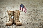 Old Military Combat Boots With Dog Tags And A Small American Flag. Rocky Gravel Background With Copy poster