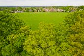 Aerial rushing forward between lush green trees towards village in English countryside poster