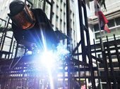 Welder On Steel Structure For Billboard Sign In Front Of The Hospital. poster