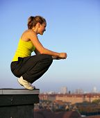 stock photo of parkour  - Young female traceur balanced on the very edge of a high urban building preparing herself mentally to participate in parkour - JPG