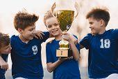Boys Sports Team Celebrating Victory. Happy Children Holding Golden Trophy. Kids Football Team Raisi poster