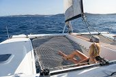 Beautiful Woman Relaxing On A Summer Sailing Cruise, Lying And Sunbathing In Hammock Of Luxury Catam poster