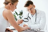 Selective Focus Of Handsome Dermatologist In Glasses Holding Magnifying Glass While Examining Woman  poster