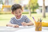Little Kid Drawing Sketching Cute Adorable. Happy Cheerful Child Drawing With Brush In Album Using A poster