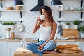 Pretty Happy Woman Sitting On The Table On The Cozy Kitchen In The Morning At Home And Drinks Coffee poster