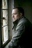 foto of sad man  - A sad man waiting and staring out of a window in an old house with natural light - JPG