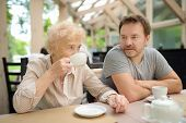Beautiful Senior Lady With His Mature Son Drinking Tea In Outdoors Cafe Or Restaurant. Elderly Lady  poster