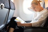 Woman Feeling Neck Pain While Reading In Flight Magazine On Long Intercontinental Airplane Flight. F poster