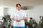 Excited Woman Measuring Her Waist At Gym. Happy Joyful Mature Lady Expressing Success After Measurin poster