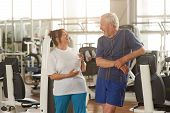 Two Happpy Senior People At Gym. Joyful Elderly Couple Laughing After A Sport Workout At Fitness Clu poster