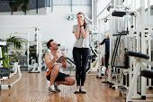 Young Excited Woman Weighing On Scale At Gym. Trainer With Client Checking Result. Human Expresion O poster