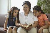 Mother reading to daughters