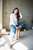 Beautiful Young Lady Artist In White Shirt Sitting Barefoot In Her Bohemian Artistic Studio Loft poster