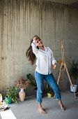 Beautiful Young Lady Artist In White Shirt Dancing Barefoot In Her Bohemian Artistic Studio Loft poster