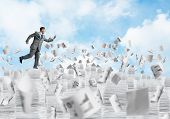Businessman In Black Suit Running With Phone In Hand Among Flying Papers With Cloudly Skyscape On Ba poster
